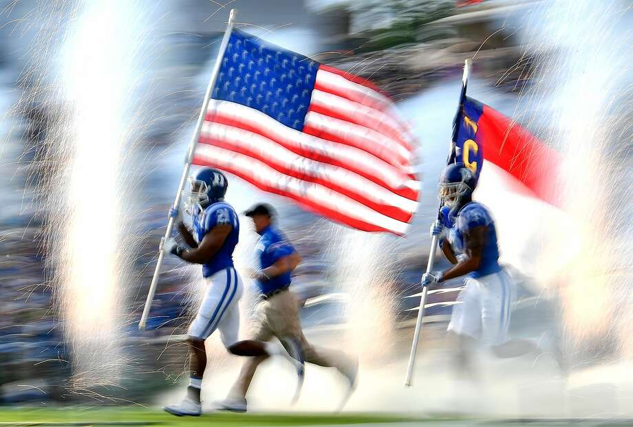 Alonzo Saxton II of Duke University carries the American flag United States flag onto the field before the Blue Devils' game against North Carolina Central on Sept. 2. Photo: Mike Comer, Getty Images