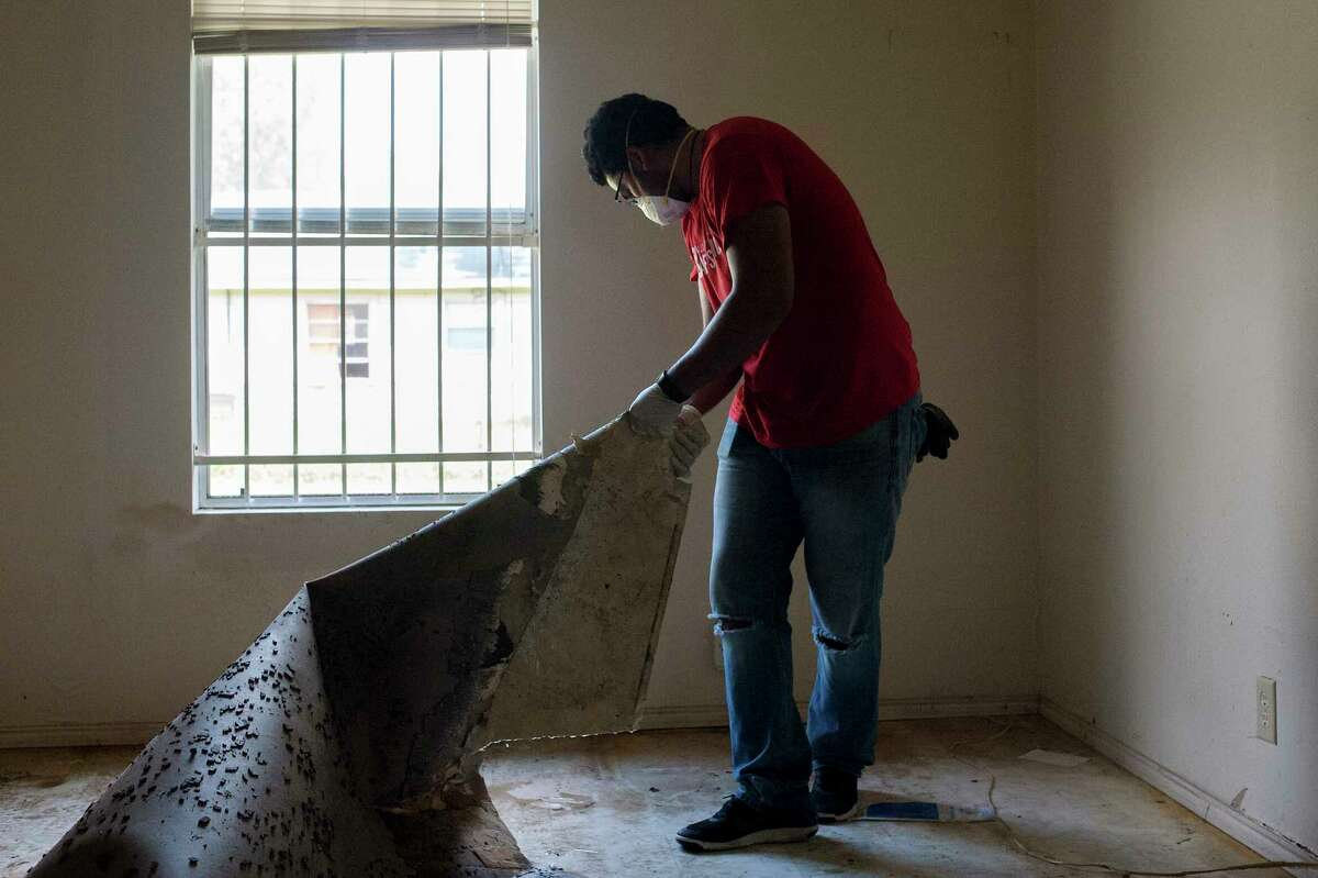Adrian Galindo cleans up a home in Kashmere Gardens on Sept. 2, 2017.