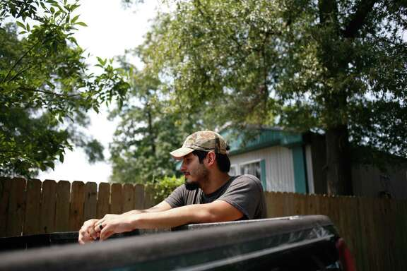"Avelino Justo, a DACA recipient, standing outside the flooded trailer home he recently purchased with his wife in Houston, Sept. 3, 2017. Some families said their choices about whether to rebuild wrecked homes may depend on whether President Trump ends a program for é""Dreamers.é• (Julie Turkewitz/The New York Times)"
