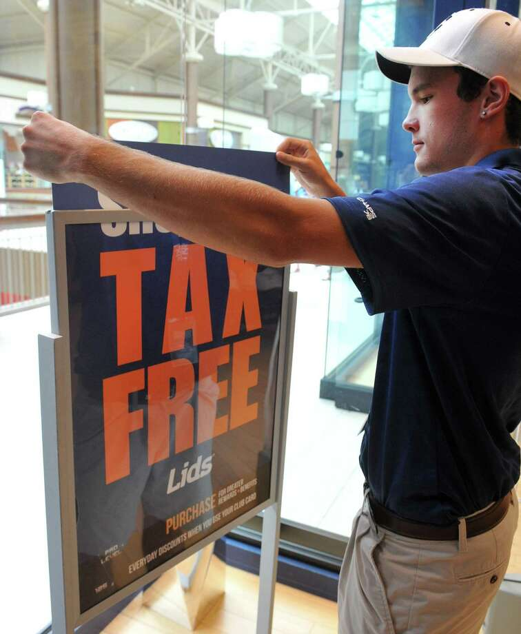 A worker places a display in the window of Lids at the Danbury Fair mall on the first day of tax free week in 2013. Photo: File Photo / The News-Times