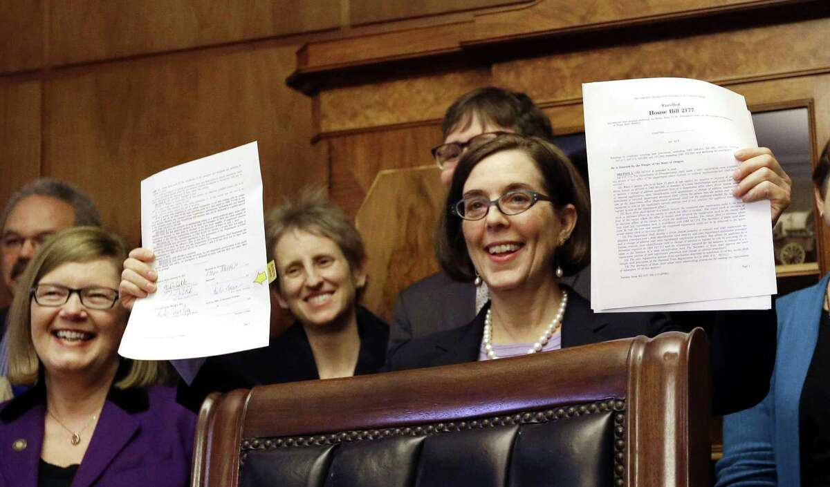 Oregon Gov. Kate Brown holds up an automatic voter registration bill after signing it March 16, 2015, in Salem, Ore. Illinois recently became the 10th state to approve a similar law. Texas should follow suit.
