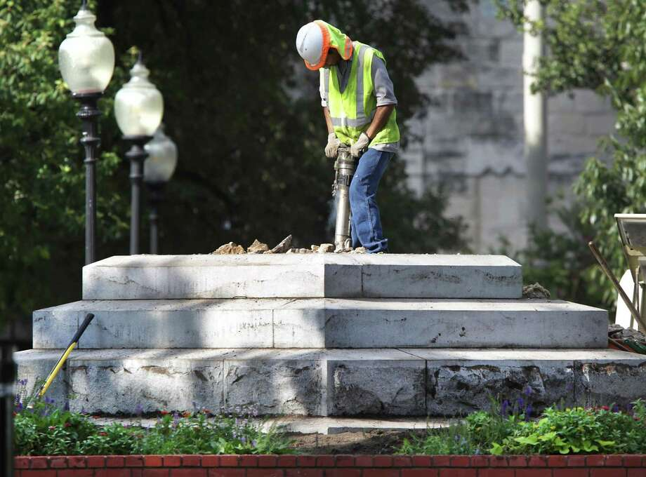 A city worker uses a jackhammer to break up and remove the base of the Confederate statue in Travis Park, on Tuesday. Police closed the park and stood guard at each entrance keeping pedestrian traffic out. Photo: Bob Owen /San Antonio Express-News / ©2017 San Antonio Express-News