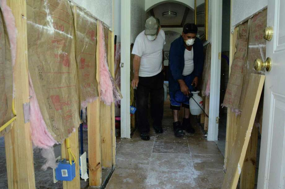 Jesus Flores, left, helps his neighbor, Jose Moreno with the first coat of a water-and-bleach mixture used to kill mold in the Brookside Village, a city northwest of Brazoria County.