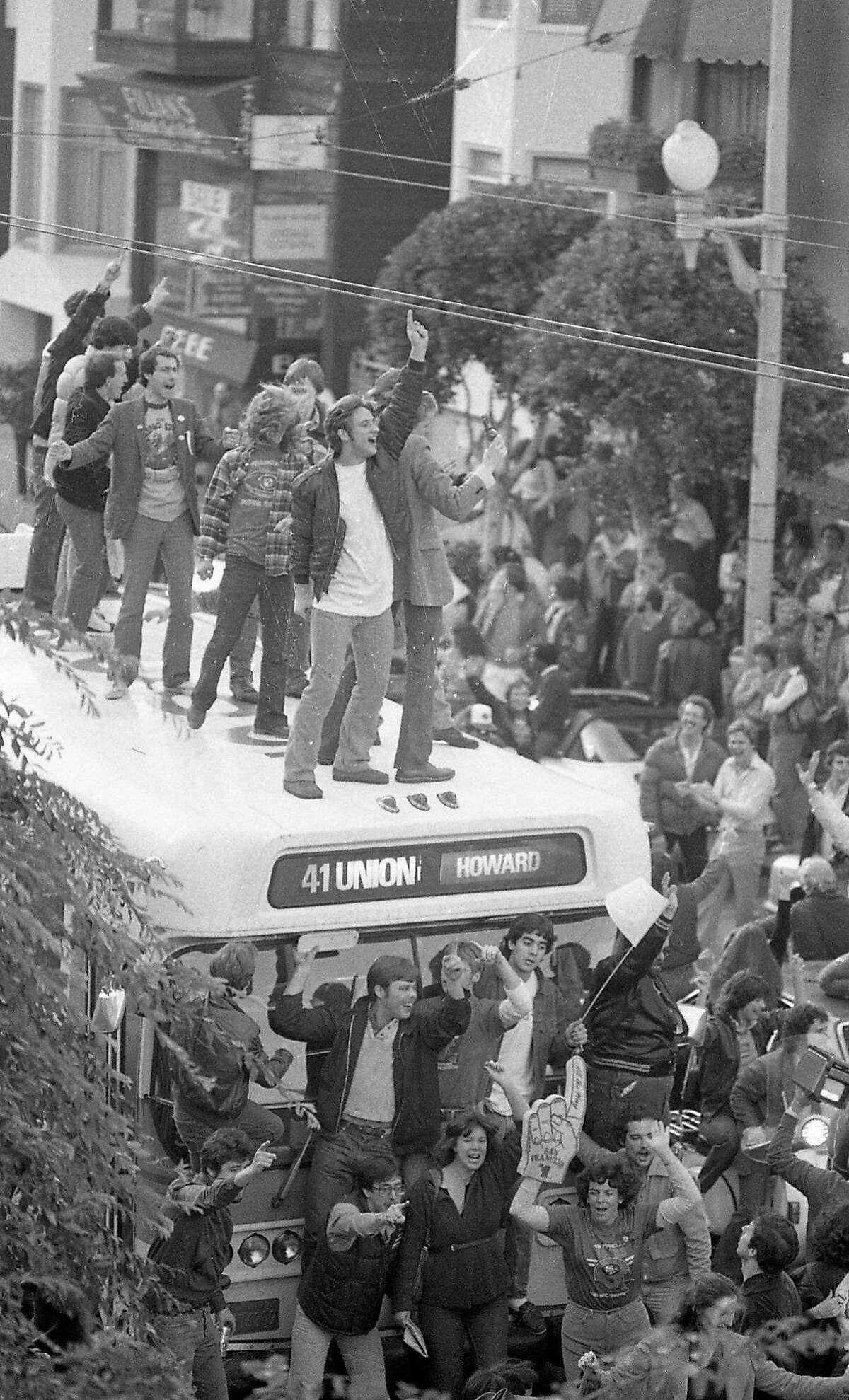 Fans celebrate the 49ers Super Bowl XVI win by climbing on top of a Muni bus on Union Street. Jan. 24, 1982.