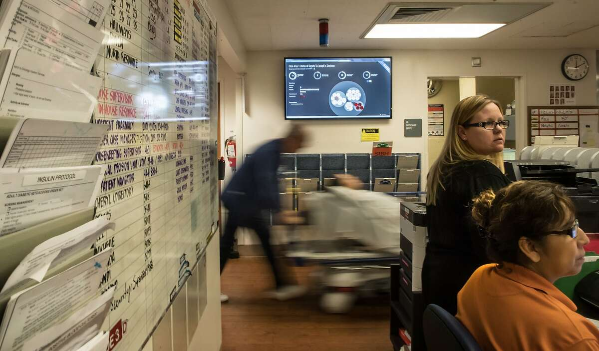 The software Qventus, on monitors in the ER at Dignity Health/St. Joseph's, keeps track of all the patients and their immediate needs on Thursday, Sept. 7, 2017 in Stockton, CA. At right is Rachelle Valdez, Patient Registration Supervisor and Leandra Uribe, an Access agent.