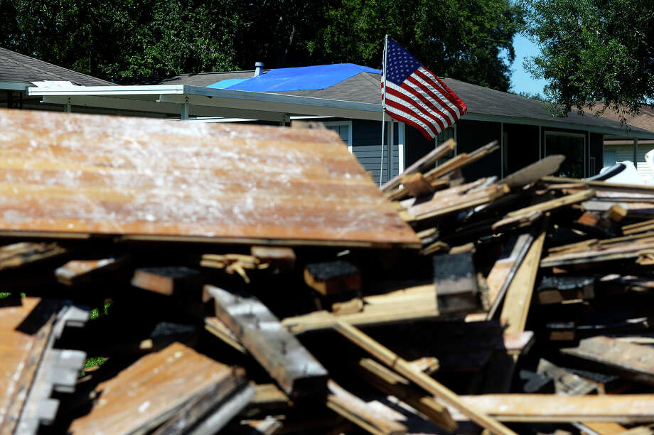 An American flag flies in a yard with a large pile of debris from flood damage in Groves.  Photo taken Thursday 9/7/17 Ryan Pelham/The Enterprise Photo: Ryan Pelham, Ryan Pelham/The Enterprise / ©2017 The Beaumont Enterprise/Ryan Pelham