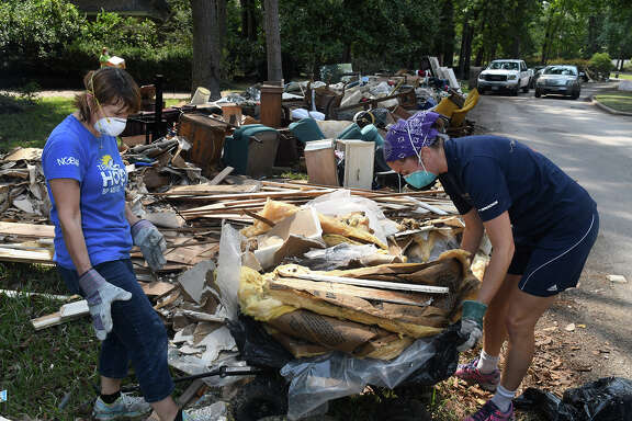Volunteers Susan Francois, left, a retired Air Traffic Controller, and Alicia Johnson, a high school Science and Engineering teacher in HISD, both of Kingwood, remove insulation and sheetrock from the flooded home owned by the parents of Leigh Ann Elkins in the Kingwood subdivision of Kings Forest on Sept. 6, 2017. (Photo by Jerry Baker/Freelance)