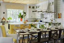 The dining area and kitchen in the 2017 Southern Living Showcase Home in the Bluejack National golf course community in Montgomery. The bright, cheerful lookiin this kitchen is a testament to the power of paint. Crisp white walls stand out against an island painted yellow and touches of yellow in captain's chairs and in the valance over the window. This luxurious lighting fits into a high-end budget, but four or five pendant lights at a lower price point could look just as chic.