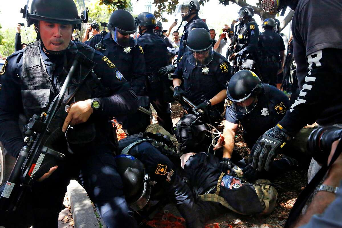 """Berkeley police officers detain someone during a rally called """"Patriot's Day Free Speech Rally"""" in Martin Luther King Jr. Civic Center Park April 15, 2017 in Berkeley, Calif."""