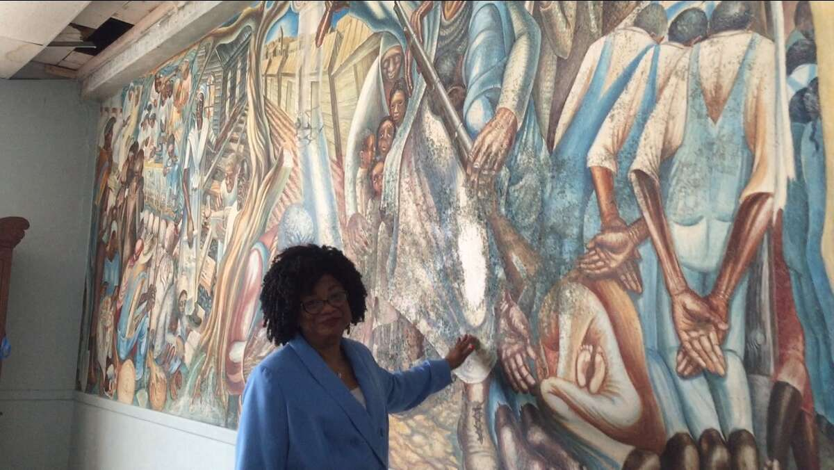 The John Biggers 1953 mural, Contribution of Negro Women to American Life and Education, covers a wall inside the Blue Triangle Multi-Cultural Association's headquarters in Houston's Third Ward. The work featuring Harriet Tubman, Sojourner Truth and Phillis Wheatley was painted when the building was operating as the Blue Triangle YWCA. A leaky roof had been threatening the mural. Caretakers pleaded in January 2016 for contributions - roughly $50,000 for a patch job and $200,000 for a complete restoration. The funding never came. In August 2017, Hurricane Harvey swept through the Houston region and sent water through the roof and walls of the historic building at 3005 McGowen. A week later, the mural has hundreds of black bursts of mold. Funders and art conservators are responding the national artistic emergency with restoration offers and money. Biggers, who founded the art department at Texas Southern University, died in 2001 at 79. He is considered one of the foremost artists who captured the black experience of the 20th century and mentored several generations of Houston artists. This photo was taken on September 8, 2017 with Blue Triangle board member Lucy Bremond.