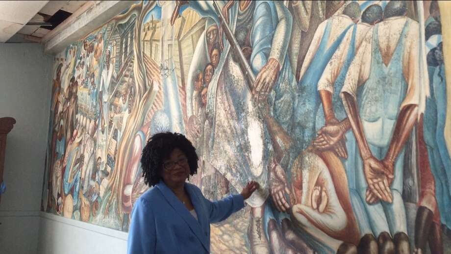 The John Biggers 1953 mural, Contribution of Negro Women to American Life and Education, covers a wall inside the Blue Triangle Multi-Cultural Association's headquarters in Houston's Third Ward. The work featuring Harriet Tubman, Sojourner Truth and Phillis Wheatley was painted when the building was operating as the Blue Triangle YWCA. A leaky roof had been threatening the mural. Caretakers pleaded in January 2016 for contributions – roughly $50,000 for a patch job and $200,000 for a complete restoration. The funding never came. In August 2017, Hurricane Harvey swept through the Houston region and sent water through the roof and walls of the historic building at 3005 McGowen. A week later, the mural has hundreds of black bursts of mold. Funders and art conservators are responding the national artistic emergency with restoration offers and money. Biggers, who founded the art department at Texas Southern University, died in 2001 at 79. He is considered one of the foremost artists who captured the black experience of the 20th century and mentored several generations of Houston artists. This photo was taken on September 8, 2017 with Blue Triangle board member Lucy Bremond. Photo: Cindy George   Houston Chronicle
