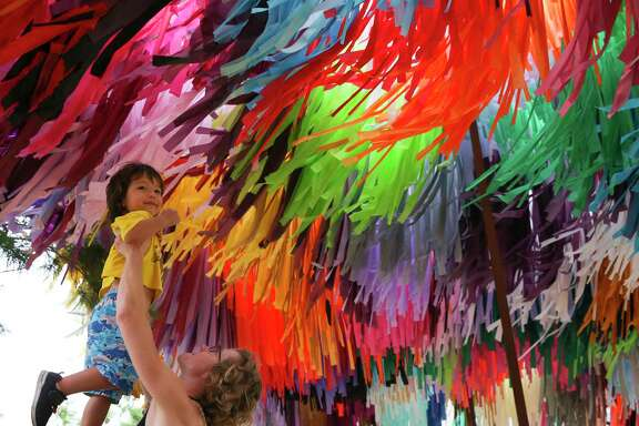 """Linde Brewer raises her son Ori Kong, 3, under """"Arcade,"""" series of streamer sculptures by Texas-based artist duo Sunny Sliger and Marianne Newsom of the Color Condition, for him to view the artwork Tuesday, Sept. 5, 2017, in Houston. The artwork will enlivening Avenida Houston through Nov. 15."""