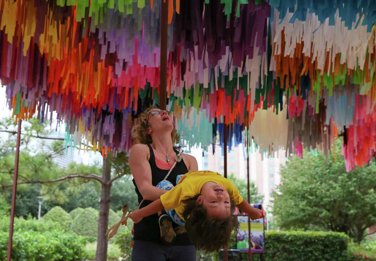 """Linde Brewer spins her son Ori Kong, 3, under """"Arcade,"""" series of streamer sculptures by Texas-based artist duo Sunny Sliger and Marianne Newsom of the Color Condition, for him to view the artwork Tuesday, Sept. 5, 2017, in Houston. The artwork will enlivening Avenida Houston through Nov. 15."""