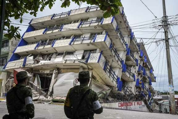 Soldiers stand guard a few yards away from the Sensación hotel, which collapsed during the powerful earthquake that struck Mexico overnight in Matias Romero, Oaxaca state. Mexico's most powerful earthquake in a century killed at least 35 people, officials said Friday, after it struck the Pacific coast, wrecking homes and sending families fleeing into the streets.