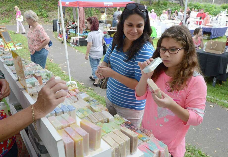 Luisa and Isabella D'Allacco from Norwalk shop for scented soaps at the Mill Pond Essentials Handmade Soap tent during the Lockwood-Mathews Mansion Museum Old-Fashioned Flea Market and antique car show in Norwalk last year. Photo: Alex Von Kleydorff / Hearst Connecticut Media File / Connecticut Post