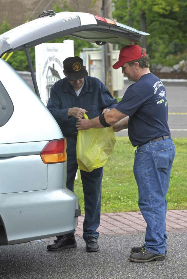 Volunteer Peter Eaton collects a donation from New Fairfield resident Thomas Buckley on Wednesday. Volunteers gathered donation dropped off at the Senior Center, in New Fairfield, for victims of Hurricane Harvey. The Stephen Siller Tunnel to Towers Foundation asked residents to drop off supplies at four locations in the Greater Danbury area. September 6, 2017, in New Fairfield, Conn. Photo: H John Voorhees III / Hearst Connecticut Media / The News-Times