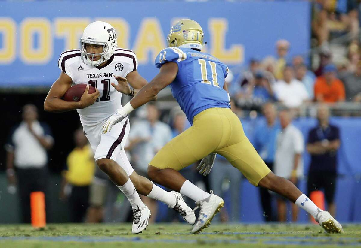 Texas A&M quarterback Kellen Mond scrambles while being chased by UCLA defensive lineman Keisean Lucier-South during the first half on Sept. 3, 2017, in Pasadena, Calif.