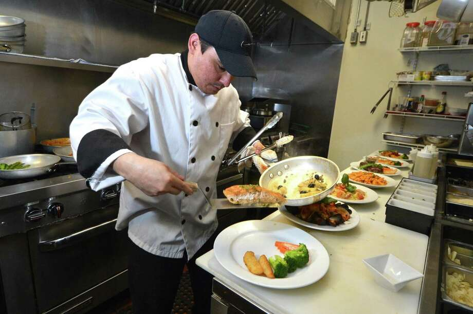 Head Chef Wilson Cardona prepares fresh Atlantic salmon during dinner service on Sunday January 22, 2017 in Norwalk Conn. at Primavera Italian Cuisine on New Canaan Ave. Primavera Restuarant is also a City of Norwalk Health Department top Lighthouse winner. Since opening in 2015, the restaurant has scored consistently high in inspections by health department sanitarians. Photo: Alex Von Kleydorff / Hearst Connecticut Media / Connecticut Post