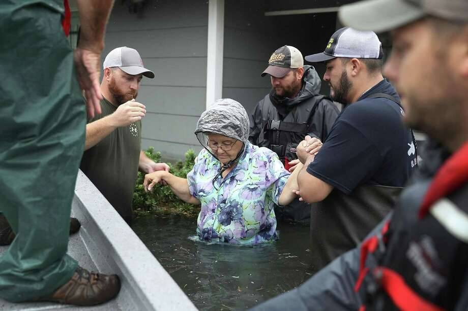 Volunteer rescuer workers help a woman from her home that was inundated with the flooding of Hurricane Harvey in Port Arthur, Texas, on Aug. 30. These and other first responders and rescuers are a heroic example of what it means to be a Texan, a reader writers. Photo: Joe Raedle /Getty Images / 2017 Getty Images