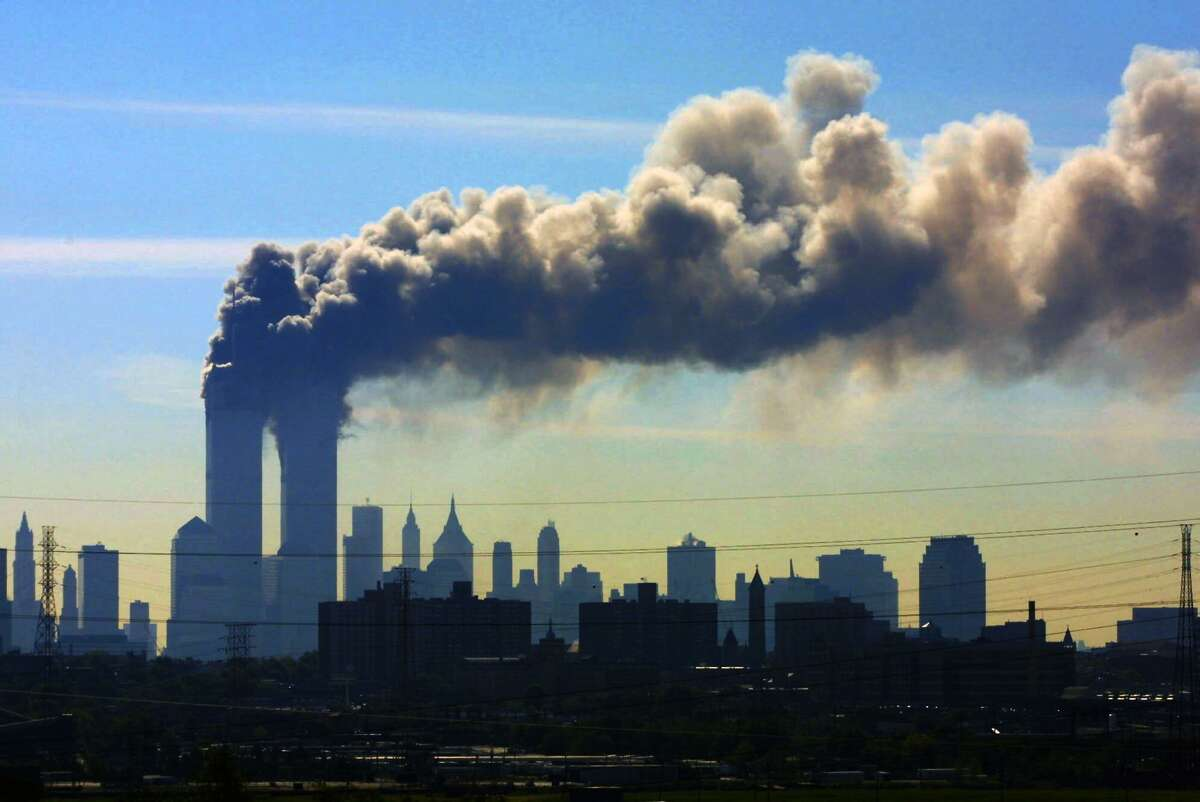 As seen from the New Jersey Turnpike near Kearny, N.J., smoke billows from the twin towers of the World Trade Center in New York after airplanes crashed into both towers on 9/11.
