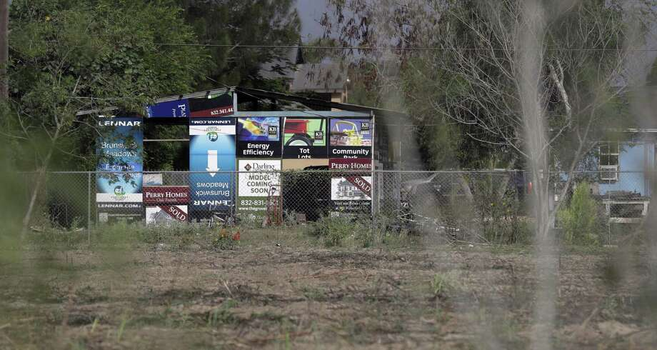 Advertising signs are used July 13 as a make-shift wall on a home in the South Tower Estates colonia near Alamo, Texas. Since the 1950s, Mexican migrants and families priced out of cities have jerry-built houses on cheap border scrubland in Texas. They need state help. Photo: Eric Gay /Associated Press / Copyright 2017 The Associated Press. All rights reserved.