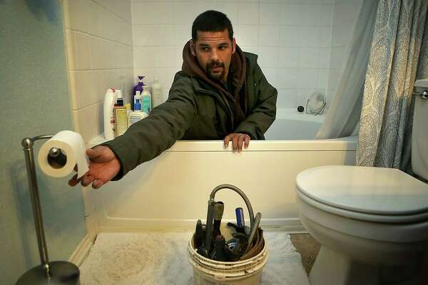 Anthony Cartagena, a San Antonio plumber, works cleaning out a bath tub drain in a client's home.