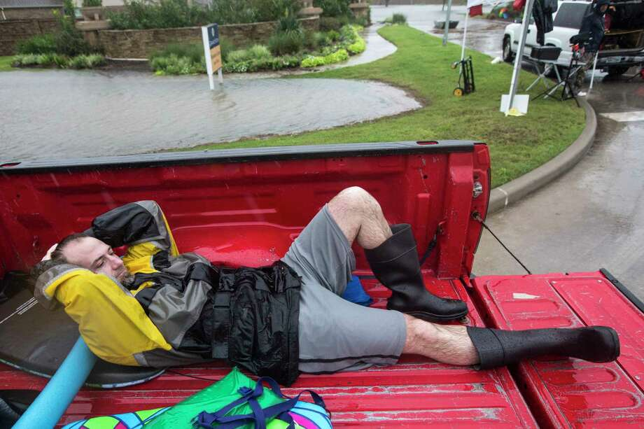 Jason Turner takes a break from helping with evacuations in the Grand Mission subdivision, as the water rises from heavy rains from Tropical Storm Harvey, on Monday, Aug. 28, 2017, unincorporated Fort Bend County, Texas. ( Brett Coomer / Houston Chronicle ) Photo: Brett Coomer, Staff / © 2017 Houston Chronicle