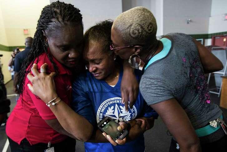 Wanda Adams, left, Rhonda Skillern-Jones, and Jolanda Jones, Houston Independent School District board of trustees members, embrace as they tour flood-damaged A.G. Hilliard Elementary School in the aftermath of Tropical Storm Harvey, on Saturday, Sept. 2, 2017, in Houston. ( Brett Coomer / Houston Chronicle )