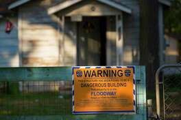 A FEMA warning sign is shown near a home damaged by floodwaters in Patton Village. More than 700,000 people have applied for assistance so far.
