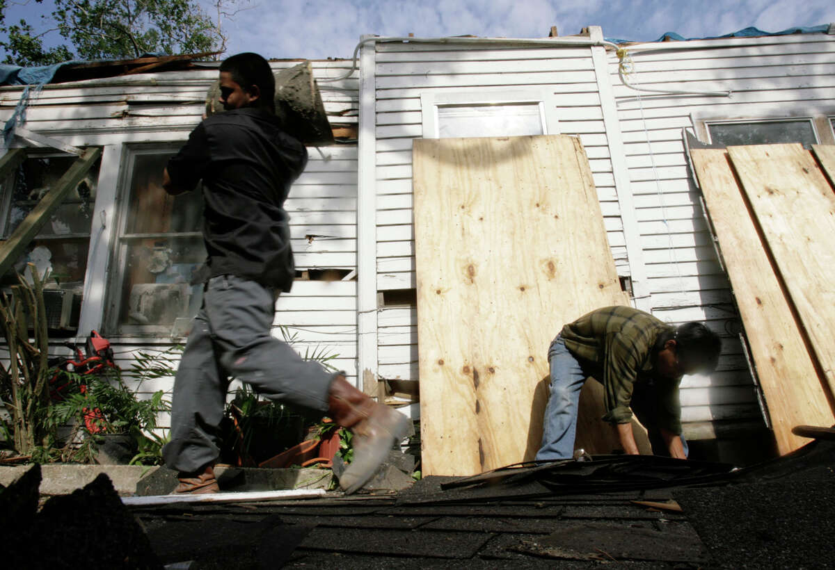 John Perriquez, 18, left, cleans up pieces of a large tree that fell on top of his great-grandmother's house during Hurricane Ike as he and Andres Gutierrez Mendez, right, a day laborer, work on cleaning up the debris from the house on Thursday, Sept. 18, 2008, in Houston. ( Julio Cortez / Chronicle )