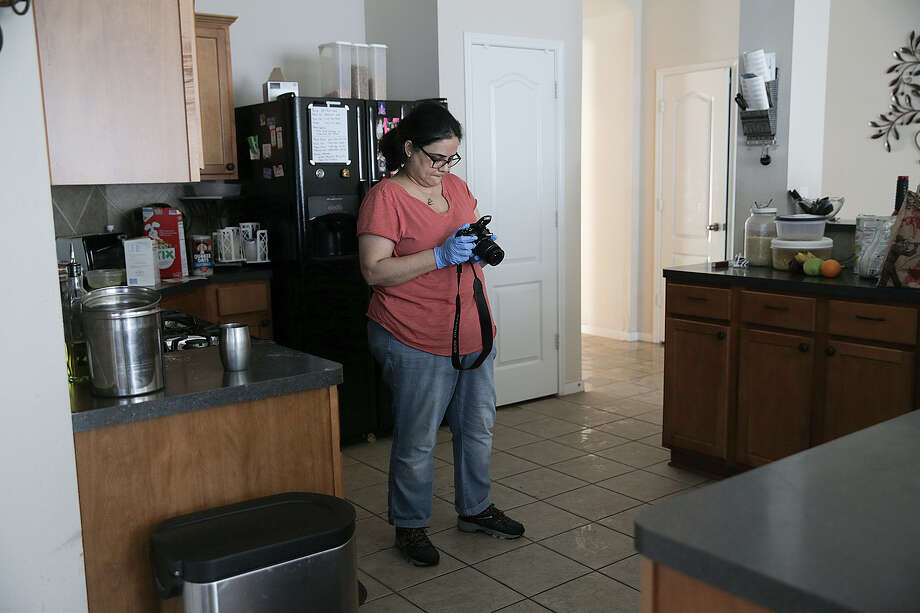 Netri Mehta takes photos of the flood damage for insurance purposes. Photo: Elizabeth Conley, Staff / © 2017 Houston Chronicle