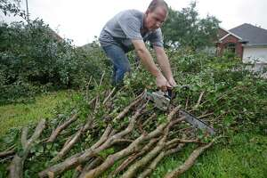 Kirby White, owner of Branchbusters, cuts a downed tree outside a home after a tornado hit the Lone Oak subdivision.