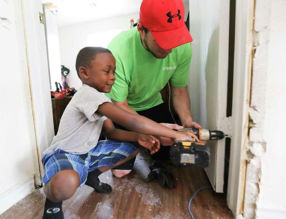 Jordan Pipkins, 6, helps volunteer Coy Custer remove screws from a door damaged in the storm. Photo: Elizabeth Conley, Staff / © 2017 Houston Chronicle