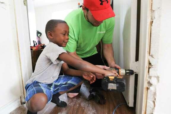 Jordan Pipkins, 6, helps volunteer Coy Custer remove screws from a door damaged in the storm.