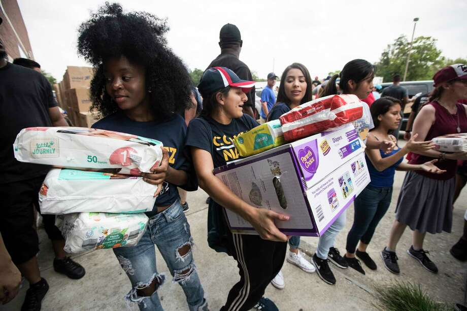 Student volunteers Nahimana Pascaziya, left, passes on diapers and helps to distribute relief supplies to people impacted by Harvey on Sunday, Sept. 3, 2017, in Houston. Photo: Brett Coomer, POOL / © 2017 Houston Chronicle