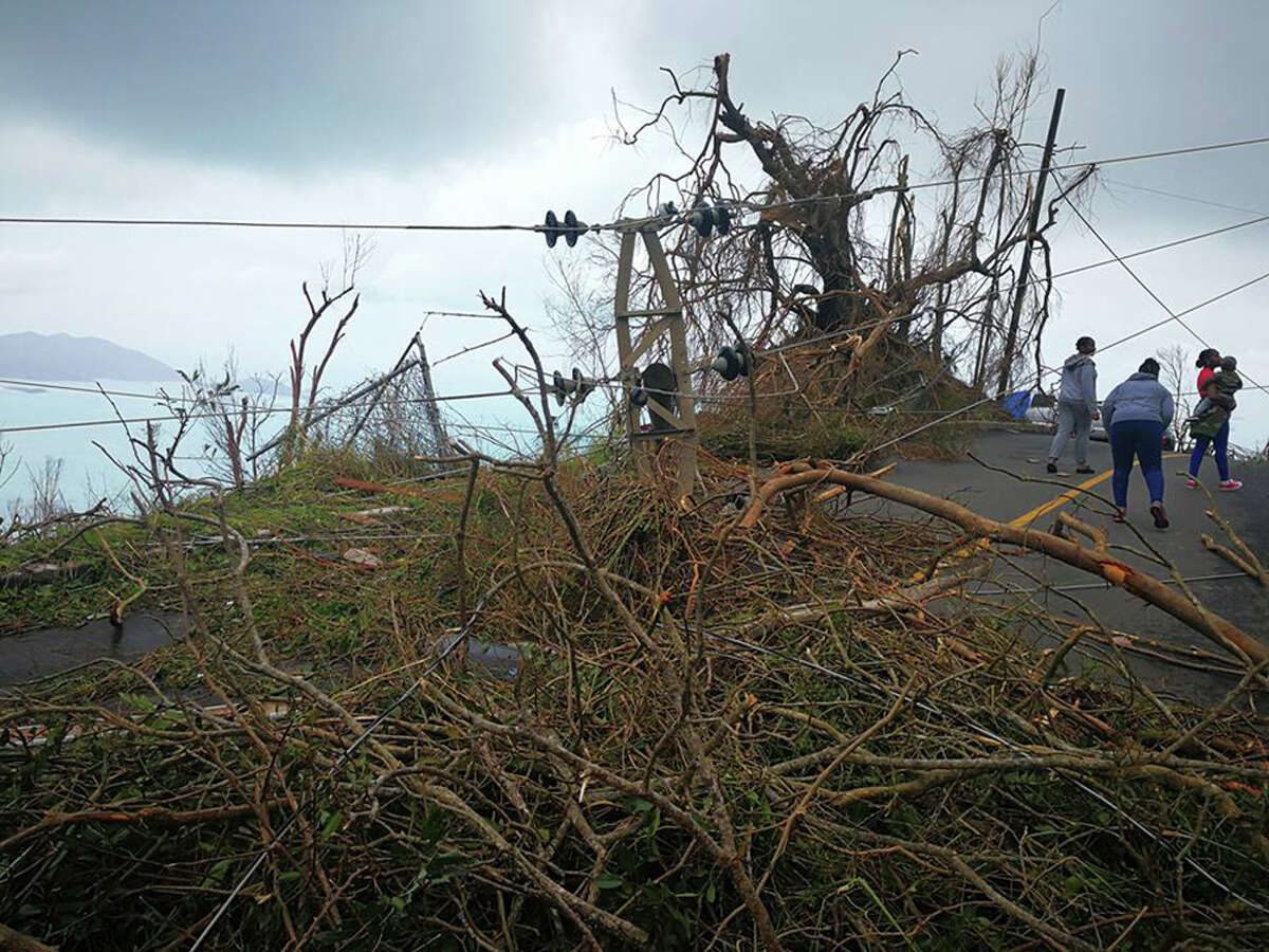 In this Thursday, Sept. 8, 2017 photo, a resident ducks under a downed power line in the aftermath of Hurricane Irma in Tortola, in the British Virgin Islands. Irma scraped Cuba's northern coast Friday on a course toward Florida, leaving in its wake a ravaged string of Caribbean resort islands strewn with splintered lumber, corrugated metal and broken concrete. (Jalon Manson Shortte via AP)