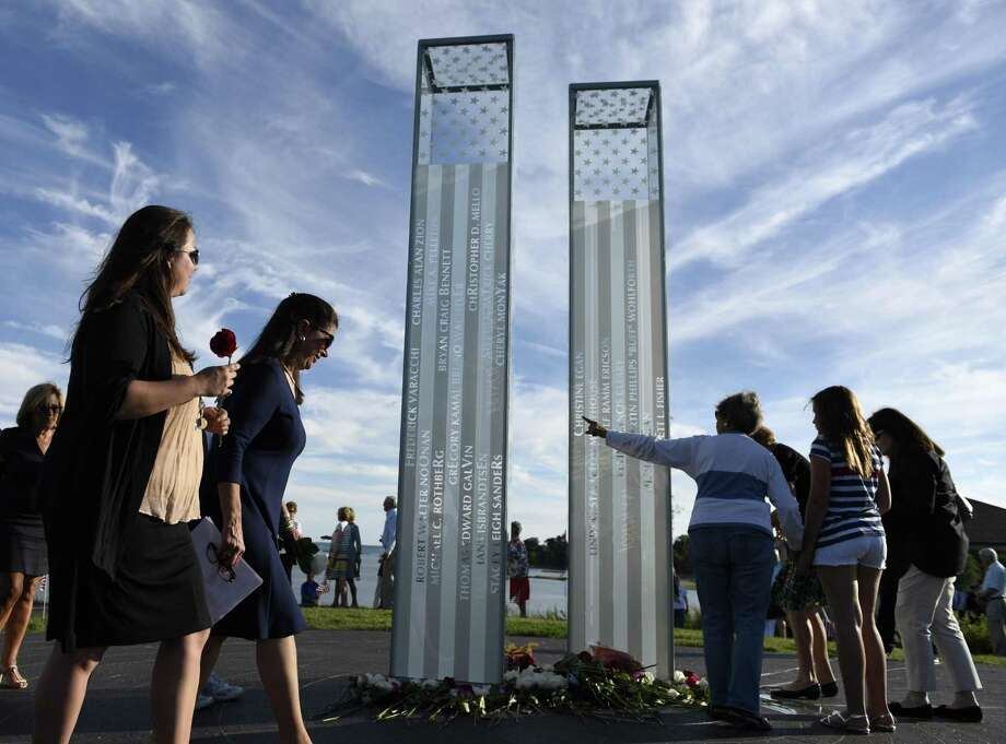 Folks place flowers at the newly-dedicated memorial during the September 11 Memorial Foundation's ceremony at Cos Cob Park in the Cos Cob section of Greenwich, Conn. Sunday, Sept. 11, 2016. More than 200 people attended the ceremony on the 15-year anniversary of the 9/11 attacks on the World Trade Center. Names of the 33 Greenwich residents lost in the attacks were read aloud, followed by a presentation of colors by the Greenwich Police and Boys & Girls Club of Greenwich honor guards and a rose-placing at the memorial. Photo: Tyler Sizemore / Hearst Connecticut Media / Greenwich Time
