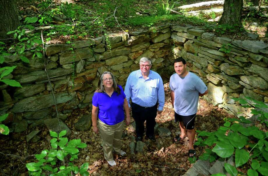 Greg Tetro, of Save Our Shelton, center, and fellow members Adrienne Couture, left, and Peter Squitieri, pose in a colonial foundation during a tour of the woods at the end of Mill Street in Shelton, Conn. on Wednesday August 9, 2017. Tetro and other members of SOS are against the proposed Towne Center at Shelter Ridge. The pre-colonial Paugussett Trail runs through the woods and a portion of it would be destroyed. The development, which is planned to be 375 apts, a retail outlet, medical and professional offices, is tied up in court. Photo: Christian Abraham / Hearst Connecticut Media / Connecticut Post