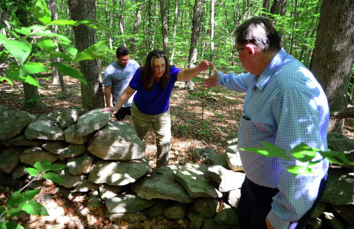 Greg Tetro, of Save Our Shelton, right, helpds fellow member Adrienne Couture, left, as she and Peter Squitieri, in back, take a tour of the woods at the end of Mill Street in Shelton, Conn. on Wednesday August 9, 2017. Tetro and other members of SOS are against the proposed Towne Center at Shelter Ridge. The pre-colonial Paugussett Trail runs through the woods and a portion of it would be destroyed. The development, which is planned to be 375 apts, a retail outlet, medical and professional offices, is tied up in court.