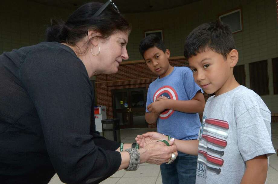 The Norwalk/Nagarote Sister City Project program manager Catherine Bagg hands out wristbands to Daniel and Emanuel Juarez, ages 11 and 9, as the organization celebrates Norwalk's Sister City, Nagarote, Nicaragua on Friday, June 16, 2017, with an informational event in front of Norwalk City Hall. Photo: Erik Trautmann / Hearst Connecticut Media / Norwalk Hour