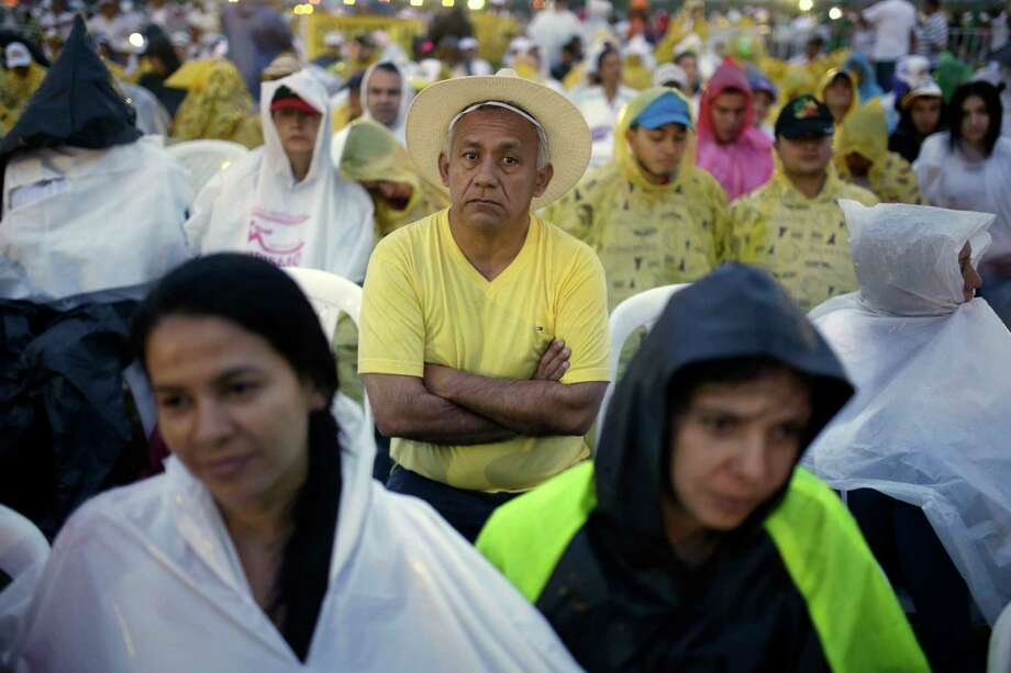 People wait in the rain for the start of a Holy Mass celebrated by Pope Francis, in Villavicencio, Colombia, Friday, Sept. 8, 2017. Francis heads Friday into an area once besieged by leftist rebels to pray with victims of Colombia's long conflict and urge them to overcome their grief by forgiving their former assailants. (AP Photo/Ricardo Mazalan) Photo: Ricardo Mazalan, STF / Copyright 2017 The Associated Press. All rights reserved.