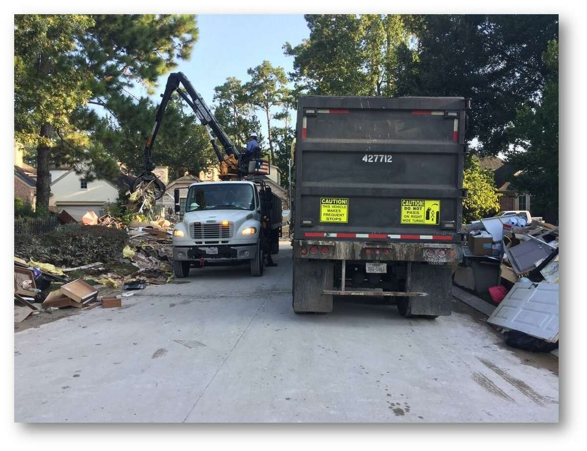 A SWM worker uses a grapple to load wreckage from the front lawn of a Houston home into a trailer. Workers have operated 12-hour shifts this week, said SWM Director David McCary.
