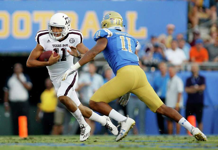 Quarterback Kellen Mond, left, scrambles against UCLA on Sunday. Mond, a true freshman, will likely start against Nicholls State Saturday night in Texas A&M's home opener at Kyle Field. Photo: Danny Moloshok, FRE / FR161655 AP