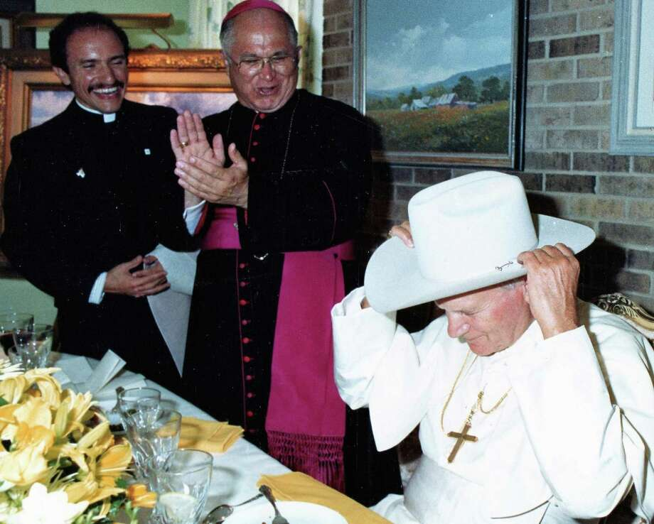 Pope John Paul II was presented with a Stetson cowboy hat at a luncheon with the Texas bishops. From the left: Fr. Michael Boulette, Archbishop Patrick Flores and Pope John Paull II. Photo: Courtesy Arturo Mari