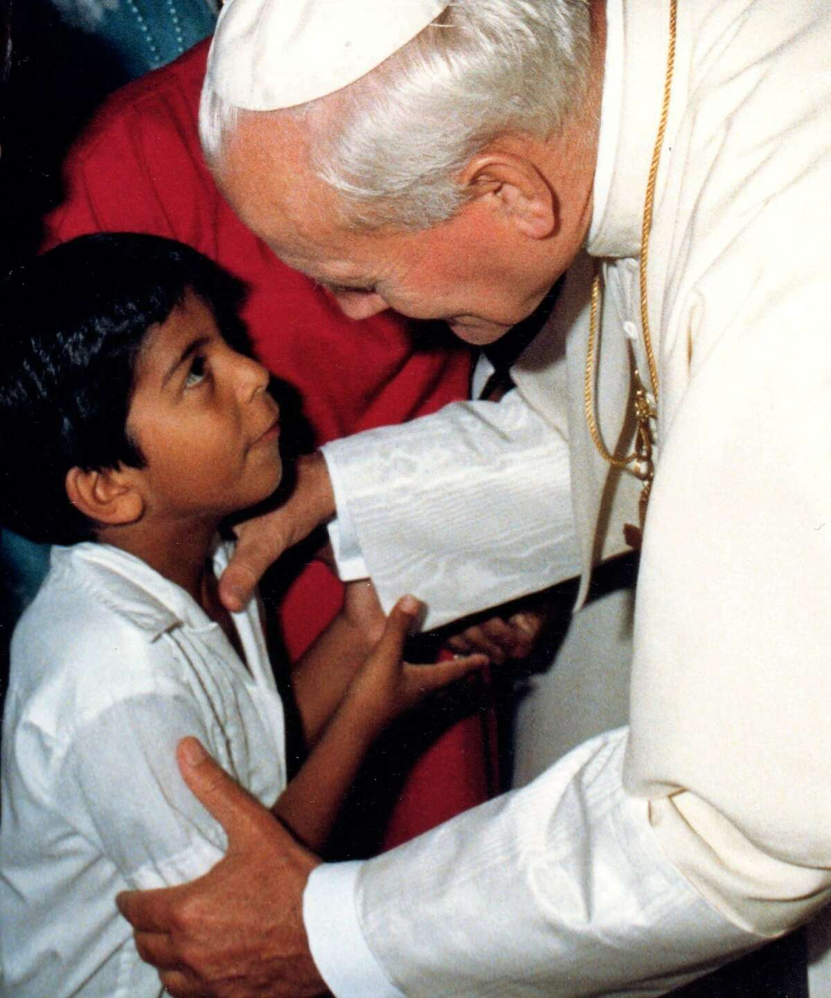 Pope John Paul II sharing a moment with 7-year-old Adam Aguirre in 1987 in San Antonio.