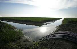 FILE - In this Feb. 25, 2016, file photo, water flows through an irrigation canal to crops near Lemoore, Calif. The California Supreme Court is set to issue a ruling Thursday, July 21, 2016, that could add millions of dollars to the governor's $15.7 billion plan to build two giant water tunnels in the Sacramento-San Joaquin Delta. (AP Photo/Rich Pedroncelli, File)