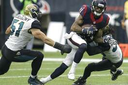 Houston Texans wide receiver Jaelen Strong (11) makes a catch between Jacksonville Jaguars middle linebacker Paul Posluszny (51) and free safety Sergio Brown (38) during the third quarter of an NFL football game at NRG Stadium on Sunday, Jan. 3, 2016, in Houston. ( Brett Coomer / Houston Chronicle )