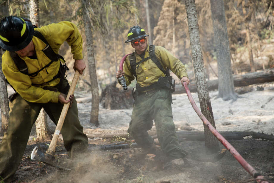 Wildland firefighters fight a small flare up on the west side of the fire line at the Norse Peak Fire, northeast of Mt. Rainier, on Friday, Sept. 8, 2017. Even a small flare needs heavy attention so it doesn't spread and takes serious digging, turning over of the soil, and hosing. Photo: GRANT HINDSLEY, SEATTLEPI.COM / SEATTLEPI.COM