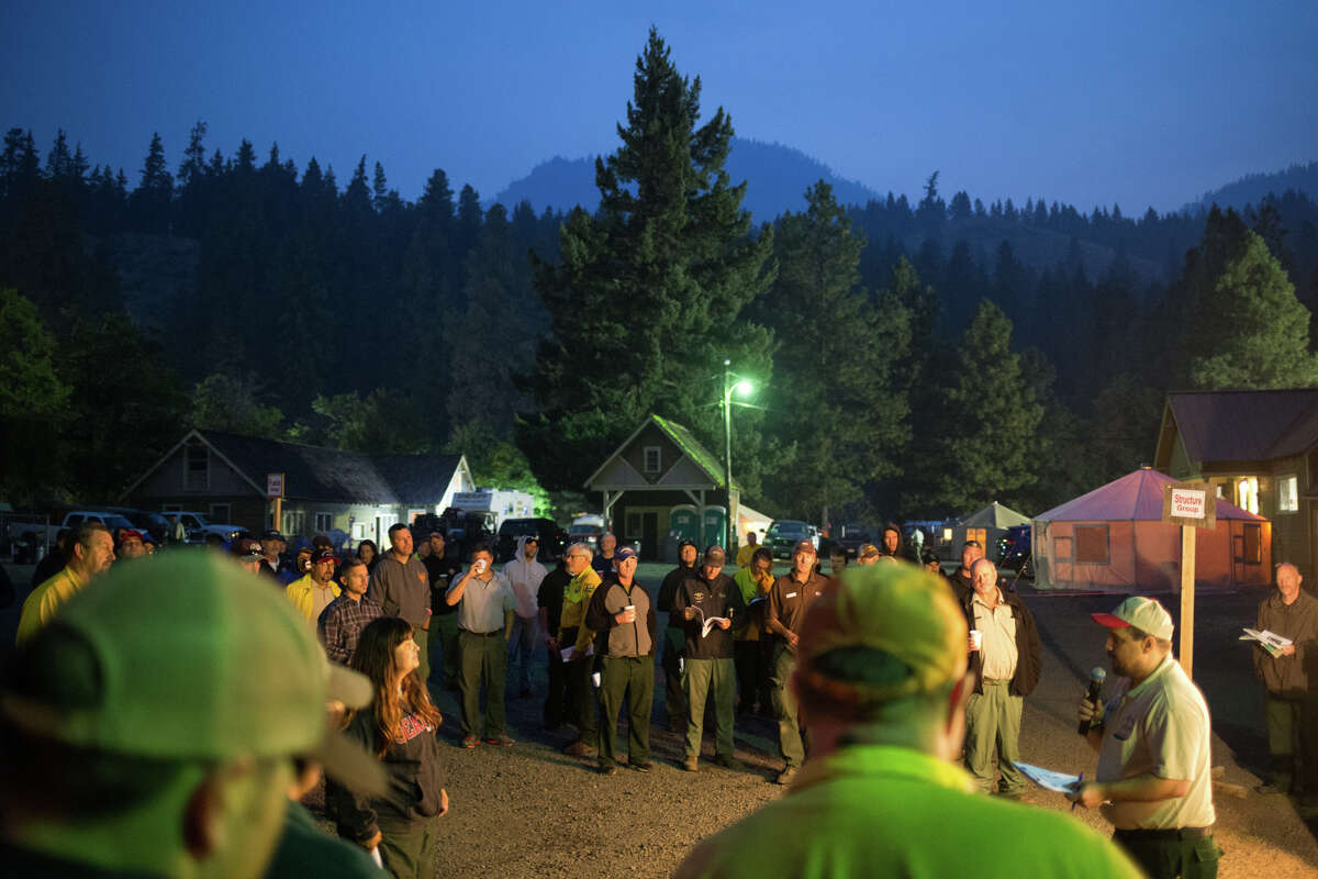 Wildland firefighters circle around for the 6 a.m. briefing at the Norse Peak Fire basecamp northeast of Mt. Rainier, on Friday, Sept. 8, 2017.