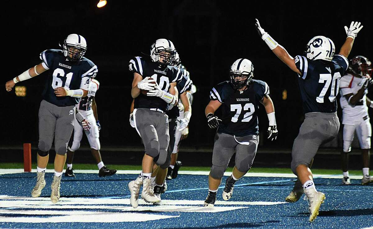 Wilton's Kyle Phillips (10) scores his second of three touchdowns and celebrates with teammates during the Warriors' 42-21 win over Brien McMahon on Friday at Fujitani Field in Wilton.